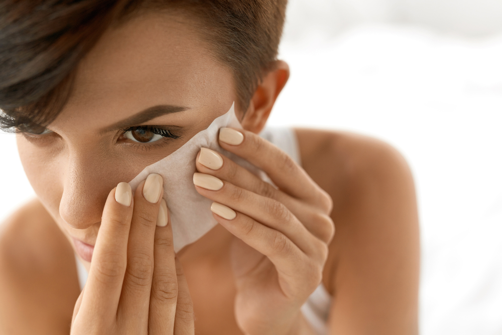 woman with face cleansing towelette