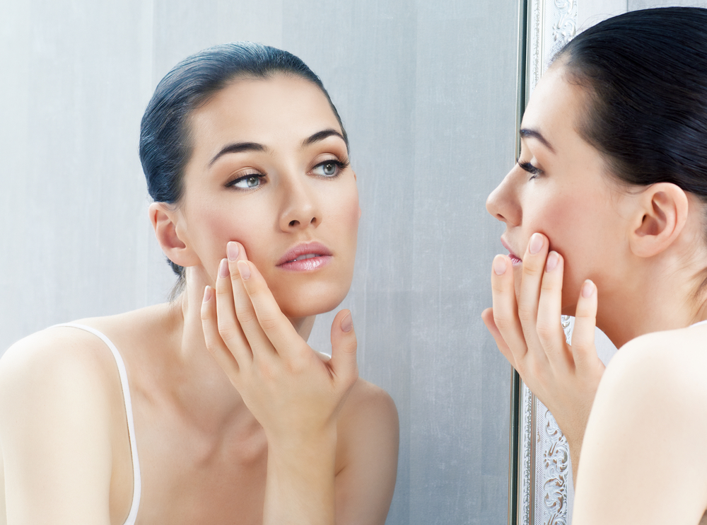 dark hair woman touching her face in front of mirror