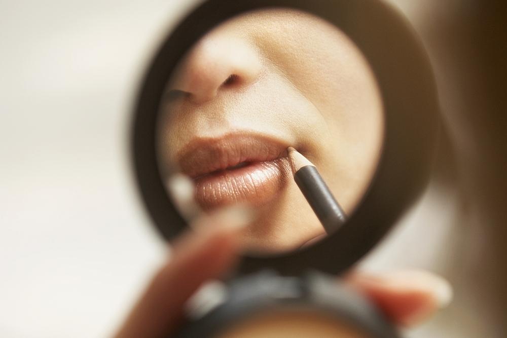 woman applying lip pencil