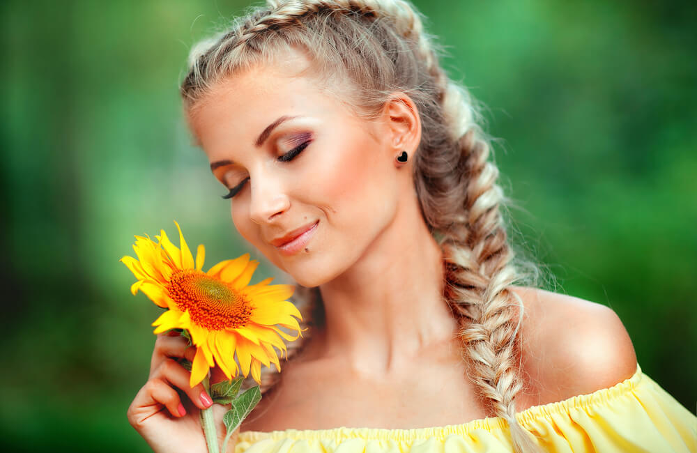 woman with braid smelling sunflower