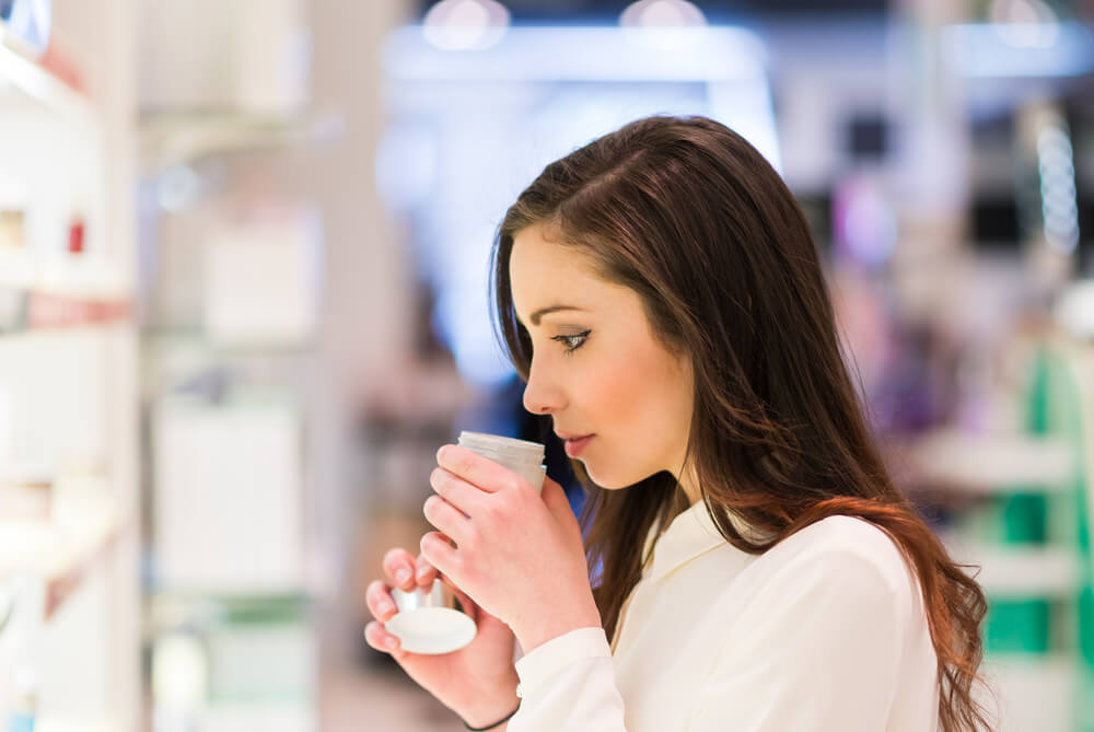 woman smelling skincare products at store