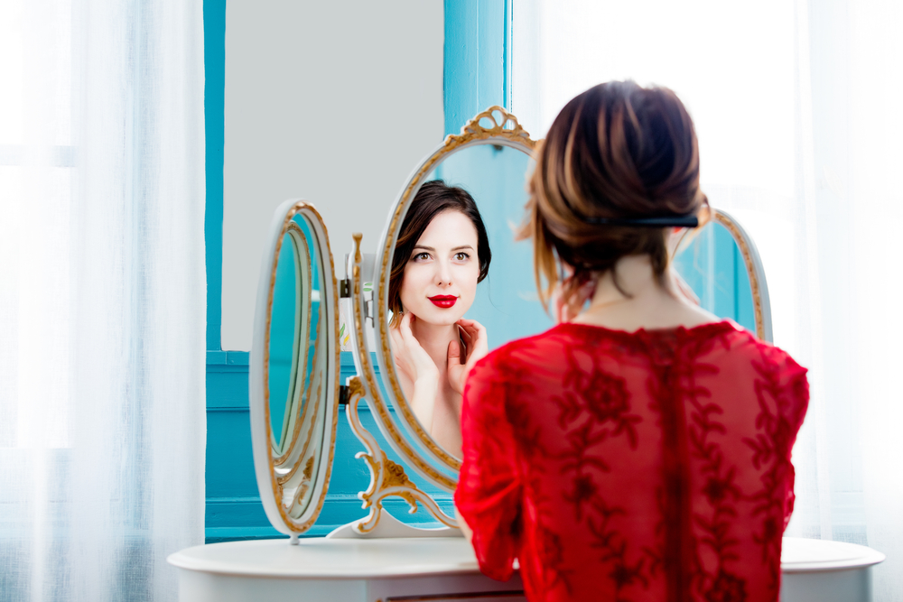 woman in red top looking at mirror